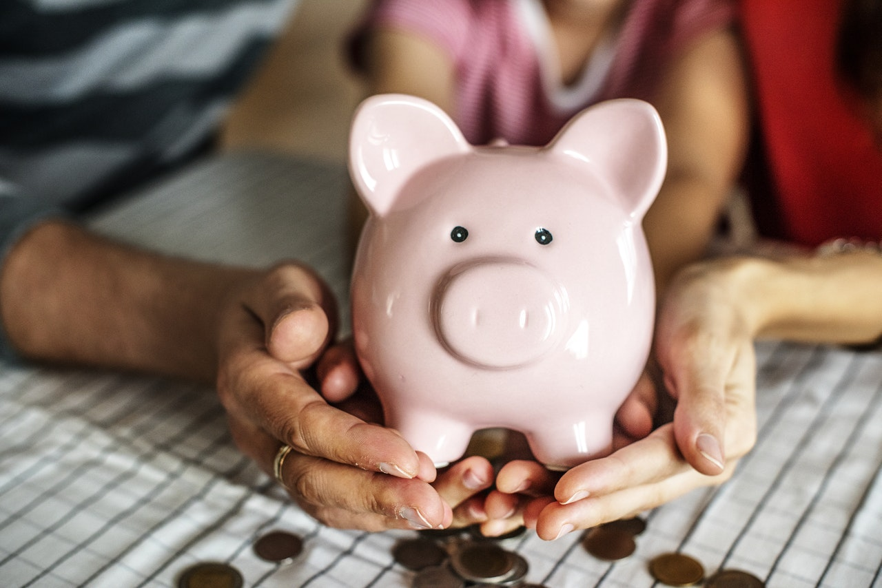 Husband and wife holding pink piggy bank filled with coins to demonstrate a martial property