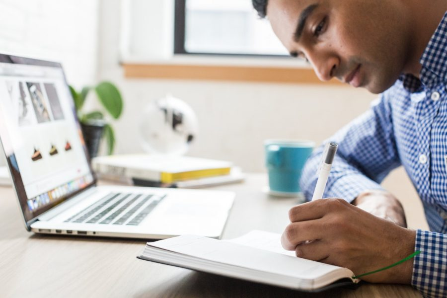Small business owner writing in notebook