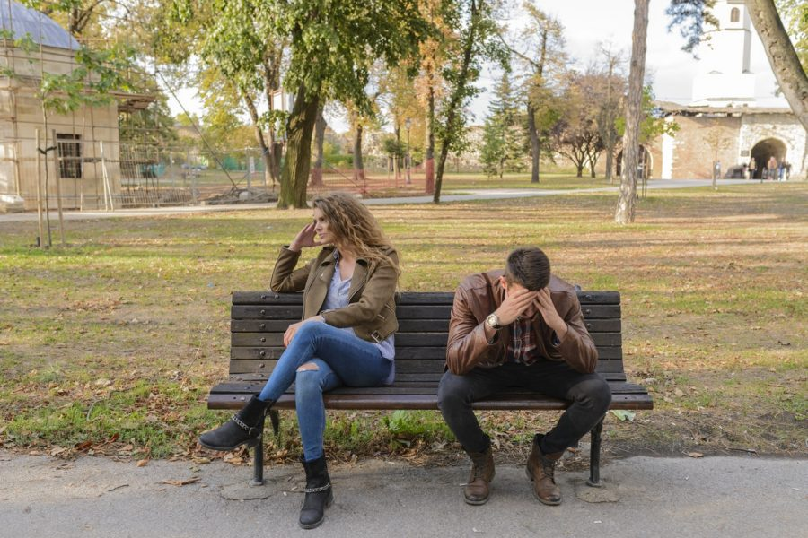woman and man sitting on bench in park fighting over divorce and 401(k)