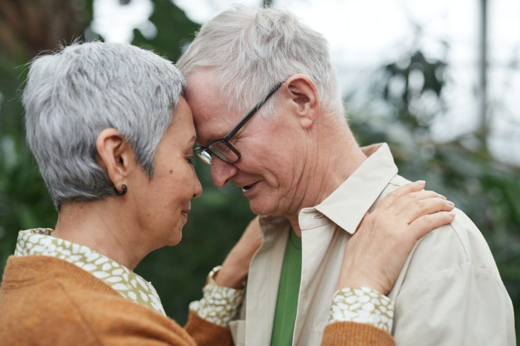 Older couple embraced in hug.