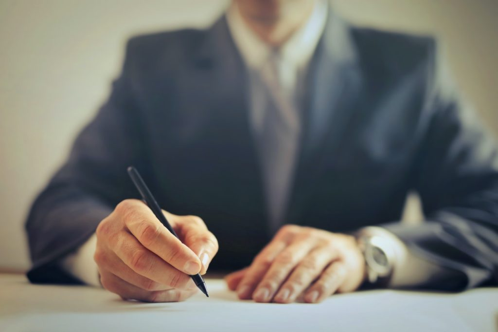 Young male lawyer holding pen over document